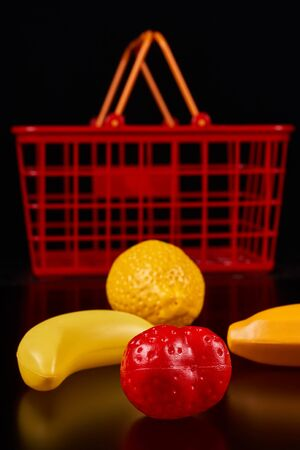 Plastic fruits lie next to a red basket on a dark background Stockfoto