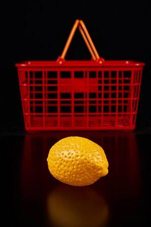 Plastic lemon lie next to a red basket on a dark background Stockfoto