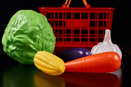 Plastic vegetables lie next to a red basket on a dark background Stockfoto