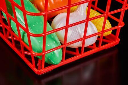 Plastic vegetables lie in a red plastic basket on a dark background. Stockfoto