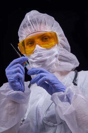 Protection against infection. The doctor is dressed in a protective suit, protective glasses and a protective mask holds a syringe with a vaccine in his hands. Isolated on a black background
