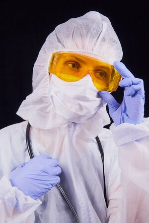 Protection against infection. A doctor in a protective suit, goggles and a protective mask and with a stethoscope adjusts his glasses. Isolated on a black background
