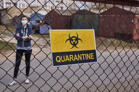 A girl is standing behind a fence with a yellow sign with the word Quarantine and a biohazard sign