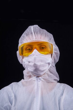 Protection against infection. The doctor is dressed in a protective suit, protective glasses and a protective mask. Isolated on a black background