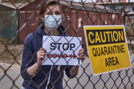 Girl with a banner saying Stop COVID-19 is behind a fence with a yellow sign with the words Caution quarantine area Stockfoto