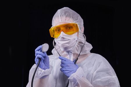Protection against infection. The doctor is dressed in a protective suit, protective glasses and a protective mask holds a stethoscope in his hands. Isolated on a black background Stockfoto