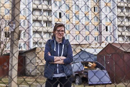 A girl with glasses stands behind a fence against the backdrop of the ghetto