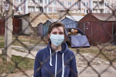 A girl in a protective medical mask stands behind a fence