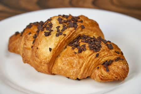 Croissant with chocolate sprinkles lies on a white plate. Close-up Archivio Fotografico