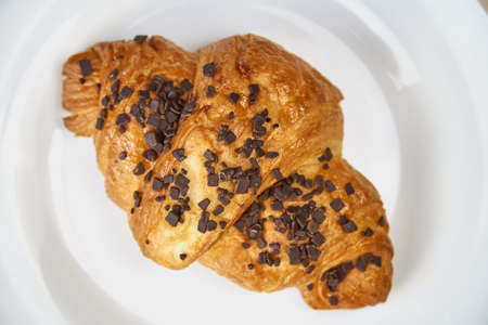 Croissant with chocolate sprinkles lies on a white plate. Flat lay