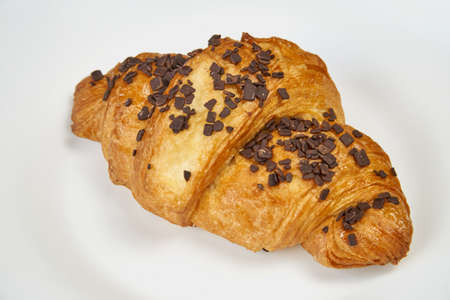 Croissant with chocolate sprinkles lies on a white plate. Isolated on white Stockfoto