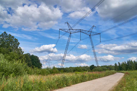 The 750 kV line support is a power distribution and transmission unit to the consumer. A large electric support standing in a field next to the road on the sky background