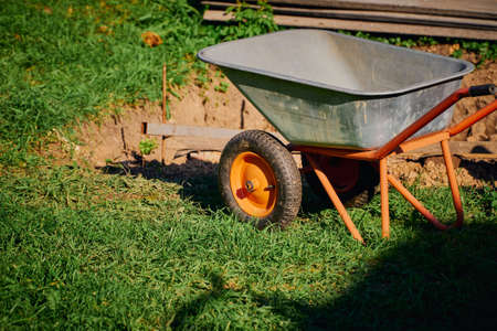 Garden work and tools. A metal garden wheelbarrow stands on a green lawn next to a dug place Foto de archivo