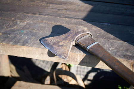 An old ax with a damaged blade lies on a wooden table Archivio Fotografico