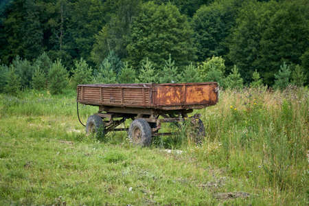 Abandoned old cargo trailer stands in a field on green grass