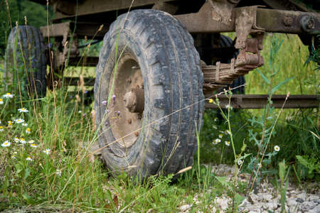 An abandoned old cargo trailer stands in a field on green grass. Trailer wheel and chassis close up