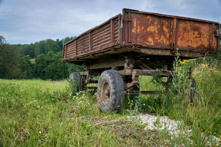 Abandoned old cargo trailer stands in a field on green grass. Close-up