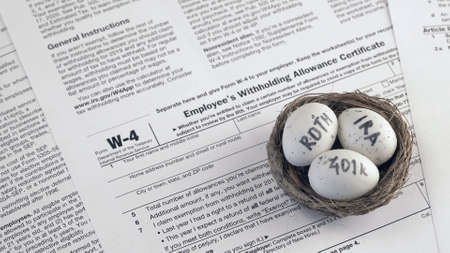 Conceptual composition. Pension savings. Individual retirement account. Three eggs with the inscriptions IRA, 401k, Roth lie in the nest against the background of the W-4 form. Close-up