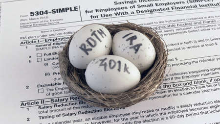 Conceptual composition. Pension savings. Individual retirement account. Three eggs with the inscriptions IRA, 401k, Roth lie in the nest against the background of the 5304-SIMPLE form. Close-up