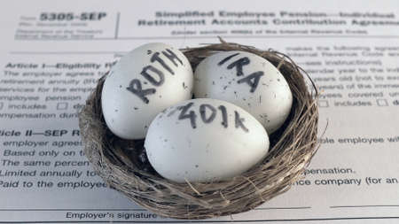 Conceptual composition. Pension savings. Individual retirement account. Three eggs with the inscriptions IRA, 401k, Roth lie in the nest against the background of the 5305-SEP form. Close-up