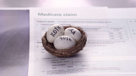 Conceptual composition. Pension savings. Three eggs with the inscriptions IRA, 401k, Roth lie in the nest against the background of the Medicare claim form. Close-up
