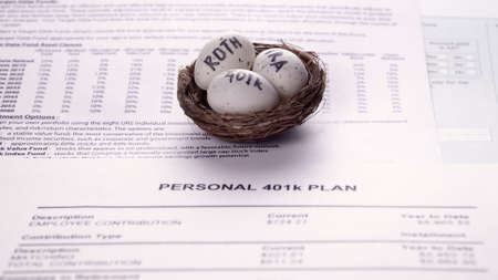 Conceptual composition. Pension savings. Individual retirement account. Three eggs with the inscriptions IRA, 401k, Roth lie in the nest against the background of the Personal 401k plan form. Close-up
