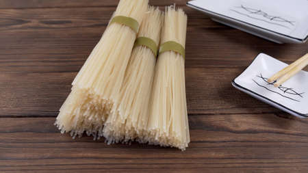 Dry unprocessed rice noodles and white square plate next to chopsticks on wooden background Foto de archivo