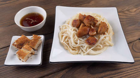 Rice noodles with fried chicken pieces in a white square plate next to fried bread and sauce on wooden background