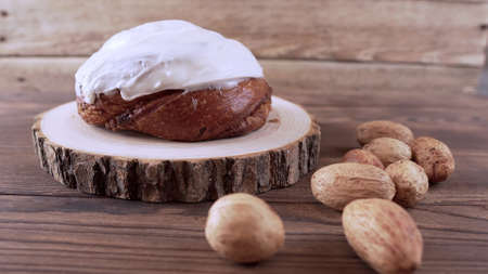 Cinnamon bun with yoghurt cream on a wooden stand standing on a wooden background next to nuts