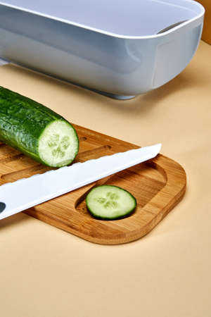 A sliced cucumber and a slice of cucumber lies next to a white ceramic knife on a bamboo cutting board near a gray food container