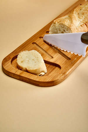 A cut baguette and a piece of bread lies next to a white ceramic knife on a bamboo cutting board