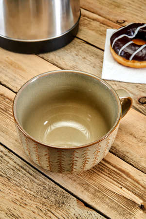 An empty brown mug stands on the table next to a donut and an electric kettle on a wooden background 版權商用圖片