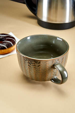 An empty brown mug stands on the table next to a donut and an electric kettle