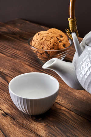 White kettle and empty white cup next to oatmeal cookies on a dark wooden background 版權商用圖片