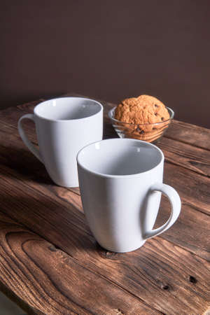 Two white empty cups and oatmeal cookies on a dark wooden background