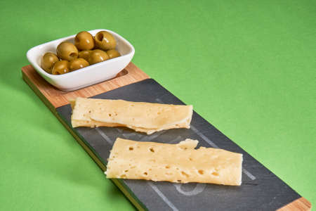 Green olives lie in a white bowl next to the sliced cheese on the chopping board on a green background