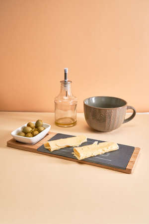 Green olives lie in a white bowl next to the sliced cheese on the chopping board, empty soup mug and empty oil bottle