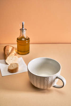 An empty soup mug stands on the table next to spices and bread