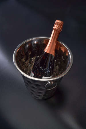 A bottle of champagne lies in a chrome bucket on a black background