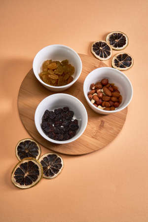 Three white flats with nuts and raisins stand on a bamboo stand. Flat lay 版權商用圖片