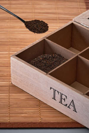 A tea box with tea on a bamboo mat. Spoon with dry tea in the foreground.