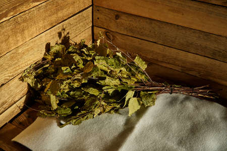 Bath supplies. Birch broom lies on a litter on a wooden bench in a steam room 版權商用圖片