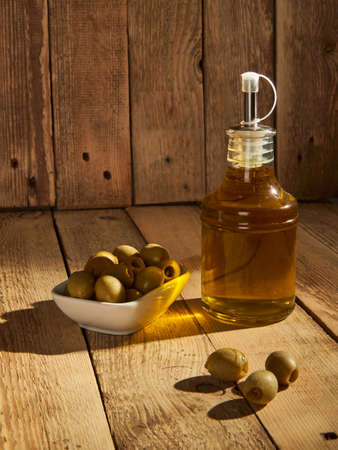 Olive oil in a bottle next to olives on a wooden background