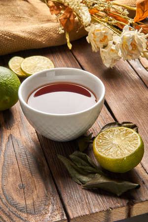 Tea in a white cup next to lime and flowers on a wooden background
