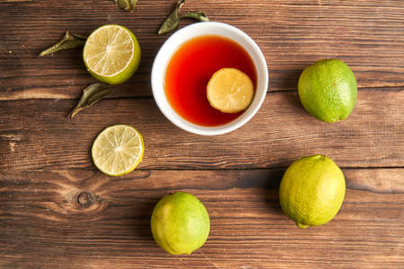 Tea in a white cup next to lime on a wooden background. Flat lay