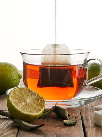Tea in a transparent cup next to a tea bag, lime and sugar on a wooden background. Water saturation with tea