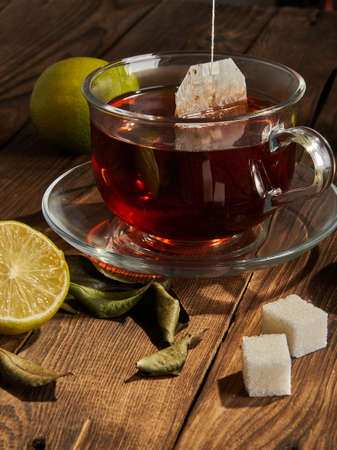 Tea in a tea bag is brewed in a transparent mug next to lime and sugar. Close-up