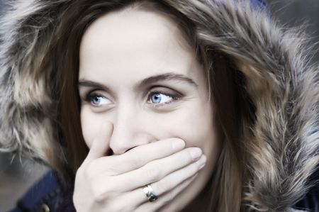 glimpse: Portrait of a laughing beautiful blue eyed young woman with a hood