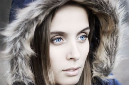 Portrait of a beautiful blue eyed young woman with a hood photo