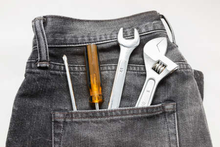 Tools in a blue jean back pocket on white background  photo